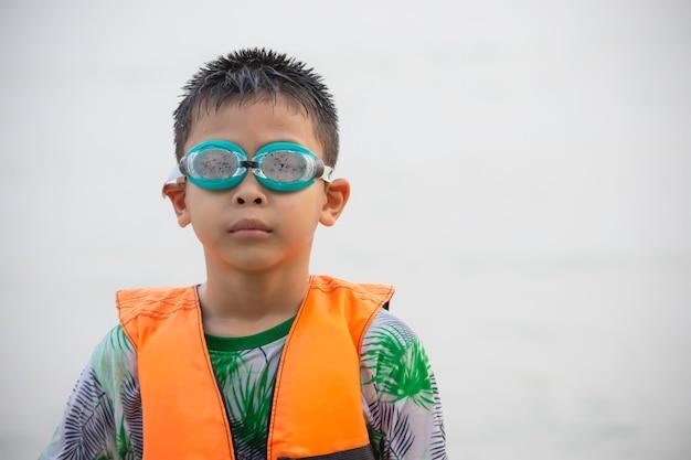 Chłopiec azjatyckich w kamizelce ratunkowej i okularach pływackich