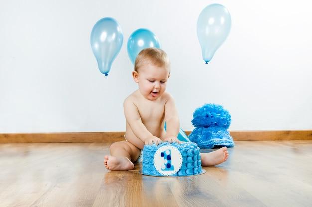 Chłopiec baby obchodzi swoje pierwsze urodziny z smakoszy ciasto i ba