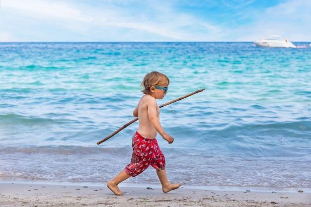 Chłopiec bawi się bambusem nad morzem na plaży