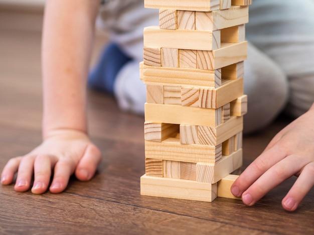 Chłopiec bawi się drewnianą wieżą