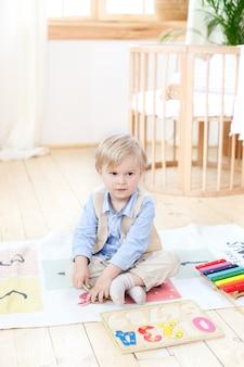 Chłopiec bawi się drewnianymi zabawkami w domu. edukacyjne drewniane zabawki dla dziecka. portret chłopca siedzącego na podłodze w pokoju dziecięcym w stylu skandynawskim. ekologiczne zabawki, wystrój pokoju dziecięcego