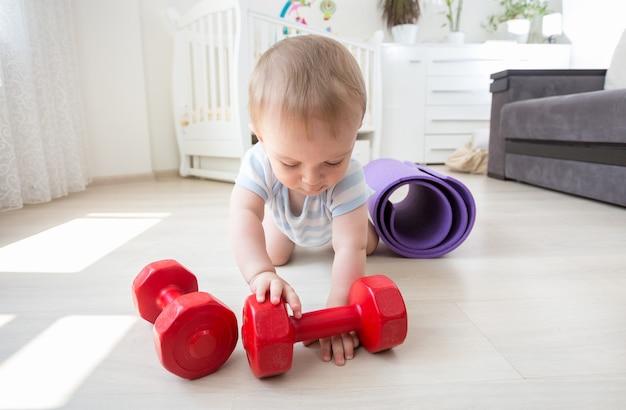 Chłopiec bawi się hantlami na podłodze w domu