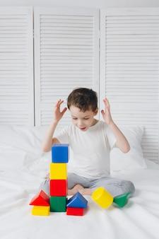 Chłopiec bawi się i buduje wieżę z kolorowych plastikowych kostek