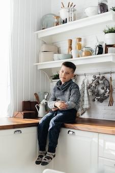 Chłopiec bawi się i je śniadanie w kuchni. szczęście. rodzina.