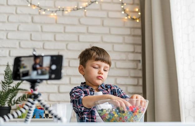 Chłopiec bawi się kulkami hydrożelu