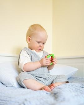 Chłopiec bawi się magnetyczną zabawką konstrukcyjną siedząc na łóżku