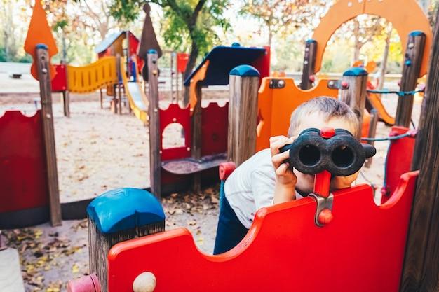 Chłopiec bawi się na placu zabaw, patrząc przez fałszywe lornetki.