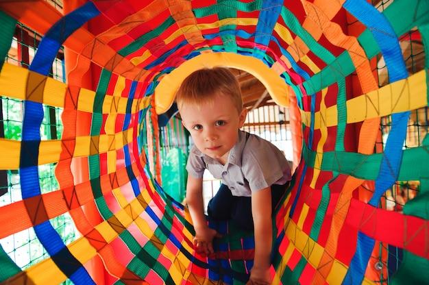 Chłopiec bawi się na placu zabaw, w labiryncie dla dzieci