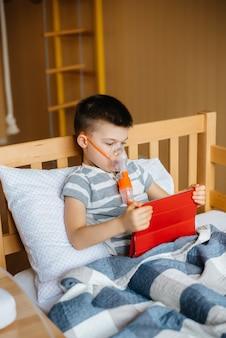 Chłopiec bawi się na tablecie podczas procedury inhalacji płuc. medycyna i opieka