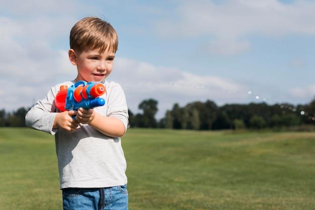 Chłopiec bawi się pistoletem na wodę