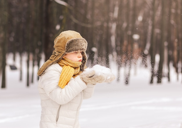 Chłopiec bawi się śniegiem w parku zimą w słoneczny dzień