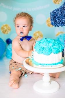 Chłopiec bawi się tortem podczas przyjęcia urodzinowego cake smash