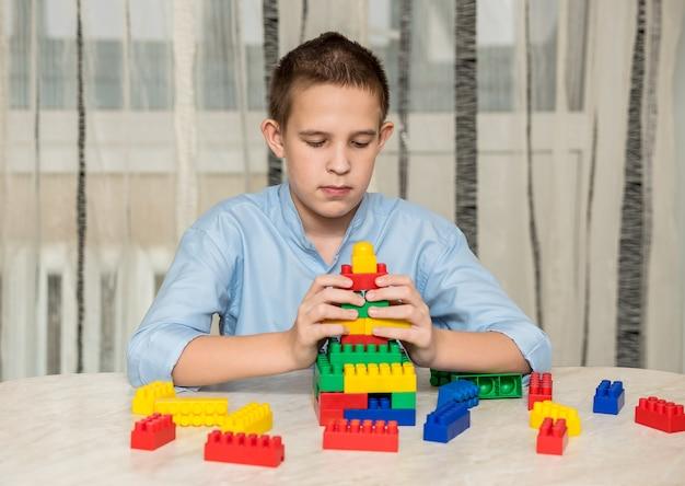 Chłopiec bawi się w domu na stole plastikowymi kostkami