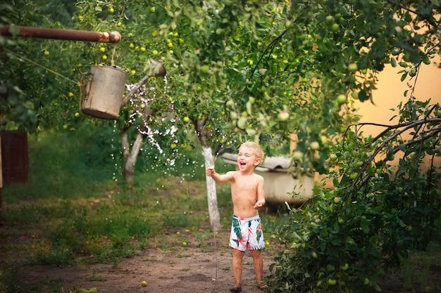 Chłopiec bawi się z bliska wody. chłopiec na podwórku otacza się wodą z konewki i kopiuje przestrzeń.