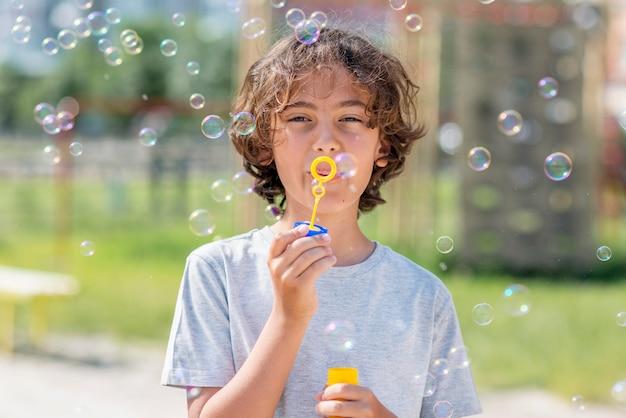Chłopiec bawi się z dmuchawy bańki