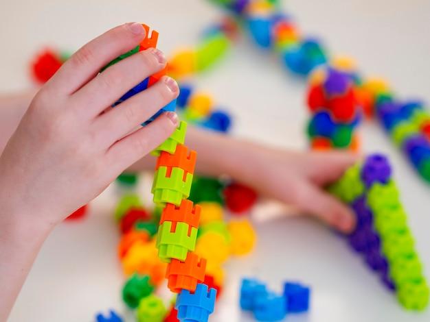 Chłopiec bawi się z kolorową wieżą