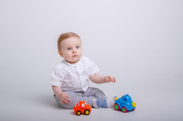 Chłopiec bawi się zabawkami samochody na białym tle