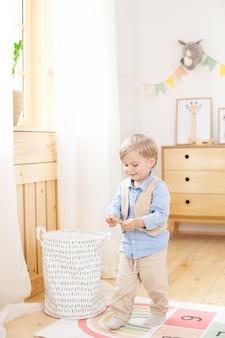 Chłopiec bawi się zabawkami w pokoju. ekologiczny wystrój pokoju dziecięcego w stylu skandynawskim. portret chłopca grającego w przedszkolu. pokój dziecięcy i aranżacja wnętrz. chłopiec jest w domu.