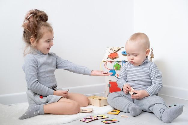 Chłopiec bawi się ze starszą siostrą z drewnianymi zabawkami. wczesny rozwój dzieci.