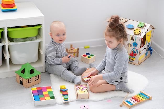 Chłopiec bawi się ze starszą siostrą z drewnianymi zabawkami