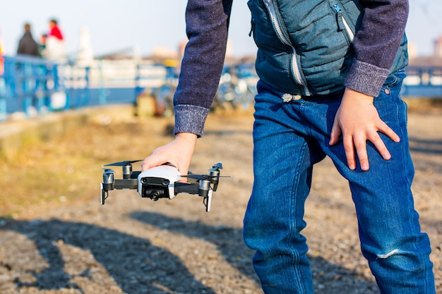 Chłopiec bawi się ze swoim dronem w parku