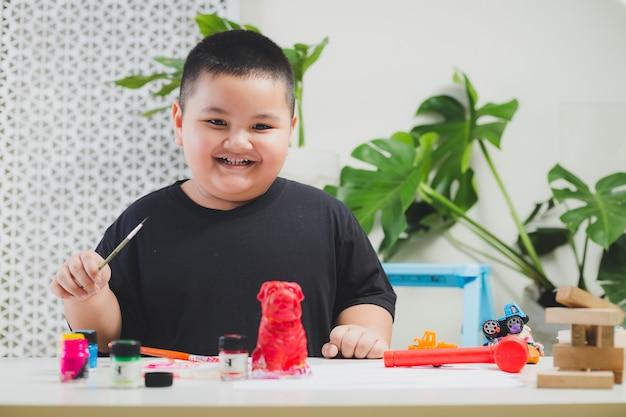 Chłopiec Bawiący Się W Domu Z Monstera Premium Zdjęcia