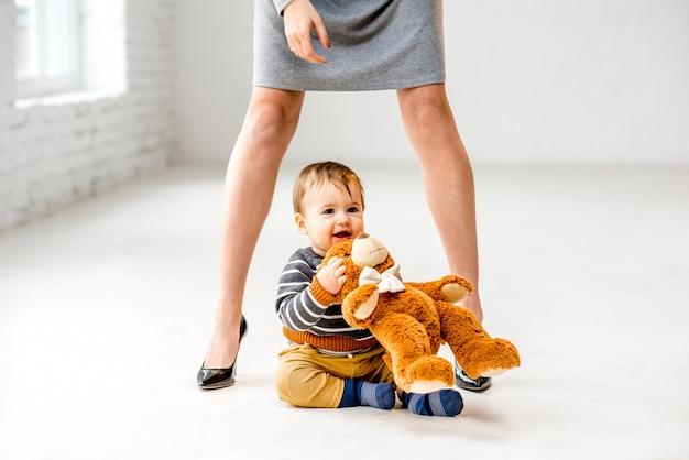 Chłopiec bawiący się w pobliżu pięknych nóg kobiety siedzącej na białej podłodze