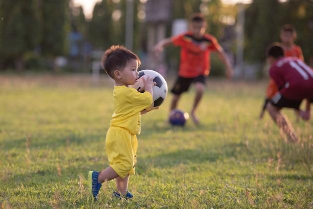 Chłopiec bawić się futbol w polu.