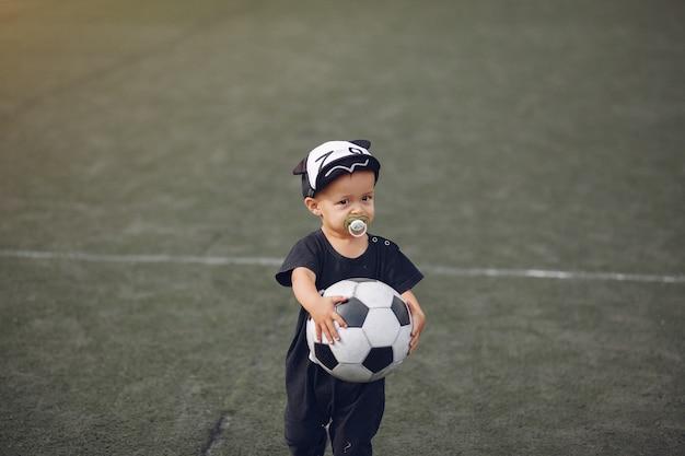 Chłopiec bawić się futbol w ziemi sportowej