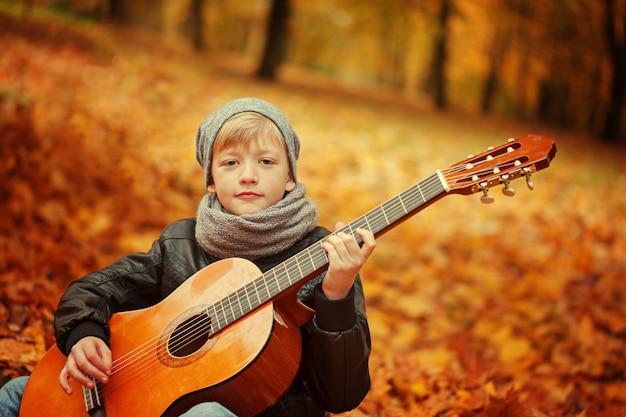 Chłopiec bawić się gitarę na naturze, jesień dzień. zainteresowanie dzieci muzyką.