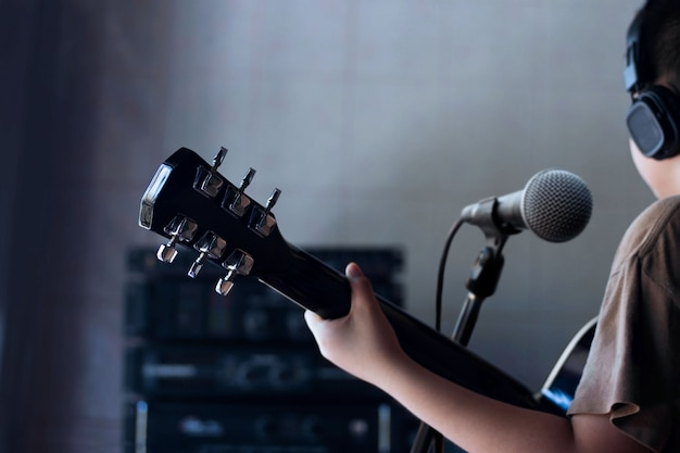 Chłopiec bawić się gitarę w dokumentacyjnym pokoju tle