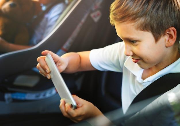 Chłopiec bawić się na smartphone w samochodzie