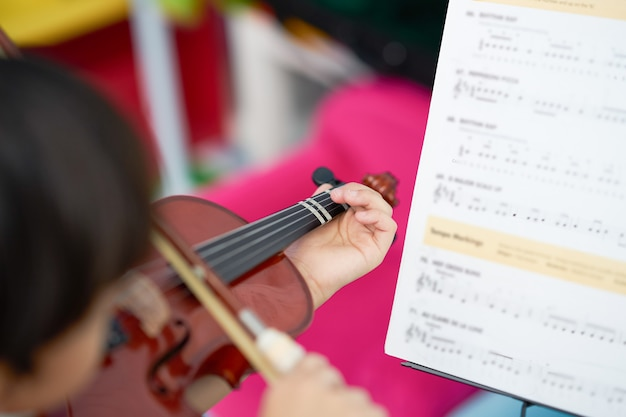 Chłopiec bawić się skrzypce z łęku sznurkiem z kopii przestrzenią na plamy tle, selekcyjnej ostrości i plamy nutowej pozyci