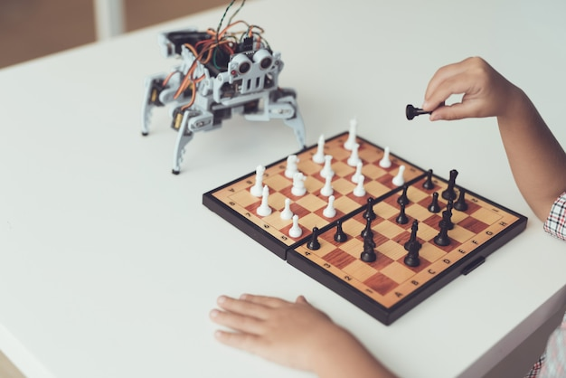 Chłopiec bawić się szachy z małym robotem przy stołem.