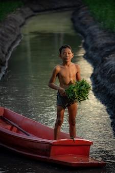 Chłopiec bawić się w warzywa uprawia ziemię blisko damnoen saduak pływającego rynku, ratchaburi prowincja