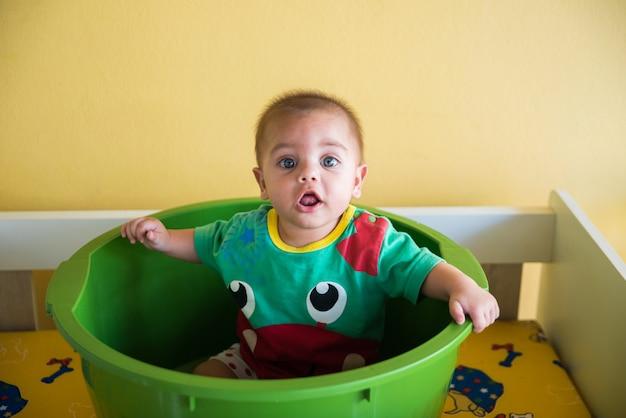 Chłopiec bawić się wśrodku plastikowego basenu