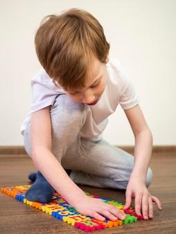 Chłopiec bawić się z abecadło grą na podłoga