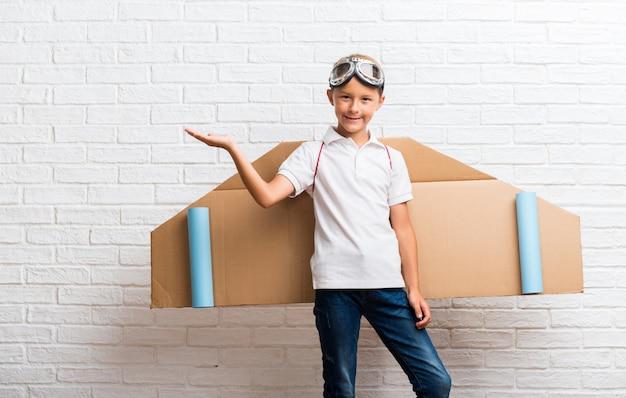 Chłopiec bawić się z kartonowymi samolotowymi skrzydłami na jego tylnym mienia copyspace imaginacyjnym na palmie
