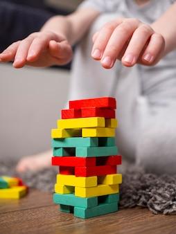 Chłopiec bawić się z kolorową drewnianą basztową grą