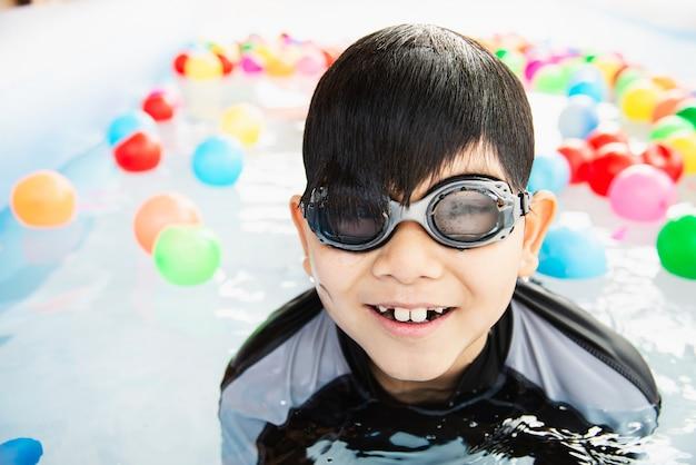 Chłopiec bawić się z kolorową piłką w małej pływackiego basenu zabawce