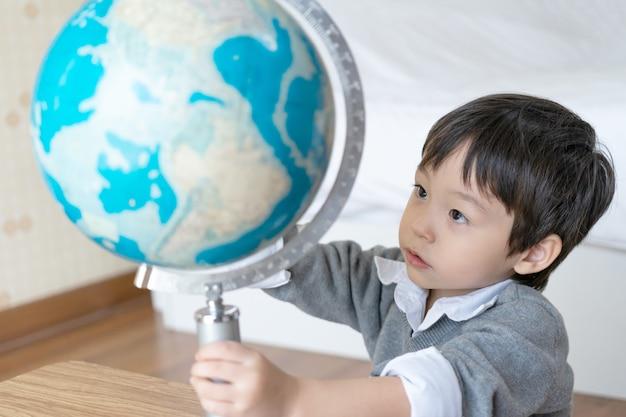 Chłopiec bawić się z kulą ziemską w domu