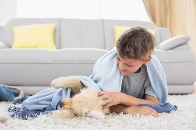 Chłopiec bawić się z szczeniaka lying on the beach na dywaniku