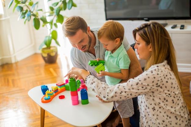 Chłopiec bawić się zabawki z matką i ojcem w domu