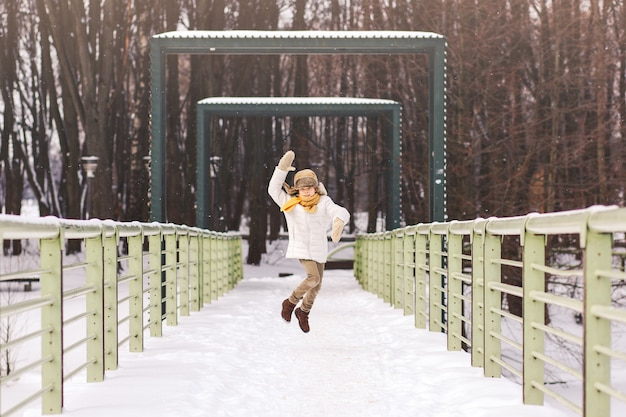 Chłopiec biegnie i bawi się zimą w parku