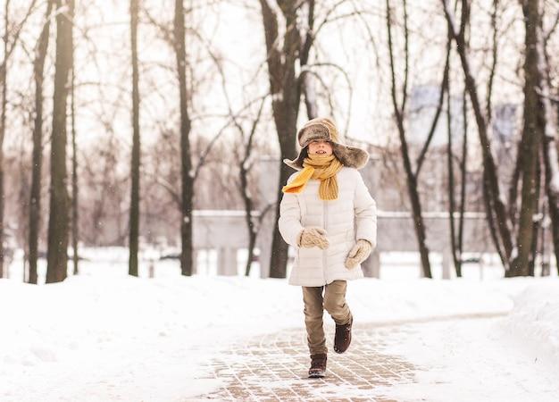 Chłopiec biegnie na ścieżce w parku zimą