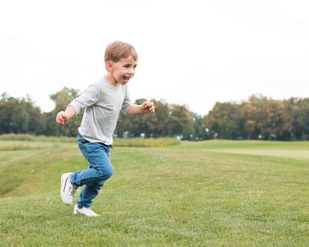 Chłopiec biegnie po trawie i jest szczęśliwy