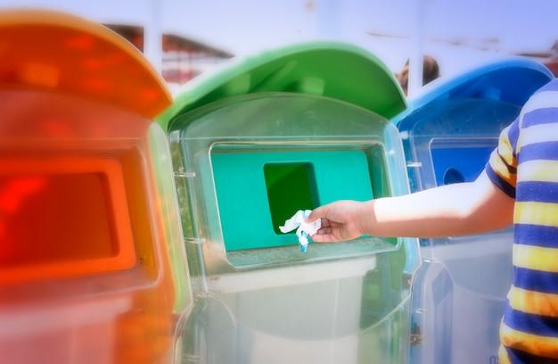 Chłopiec bierze śmieci do kosza w parku. wyrzucał śmieci z butelek.