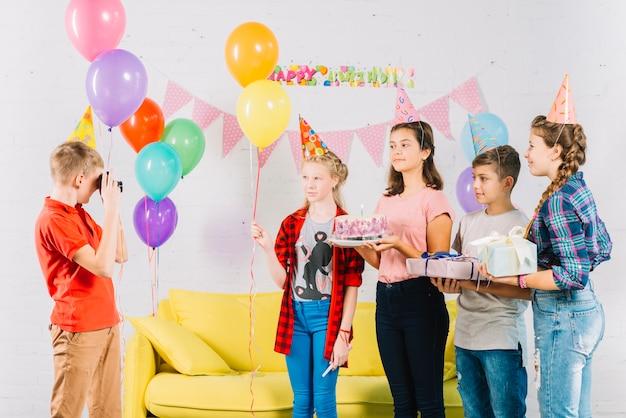 Chłopiec biorąc zdjęcie swoich przyjaciół z tort urodzinowy; prezent i balony