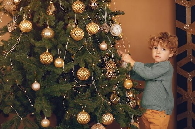 Chłopiec blisko choinki w szarym pulowerze
