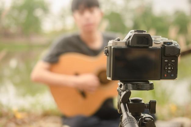 Chłopiec blogger pokazujący grę na gitarze z obserwatorem na fanpage przez internet 5g